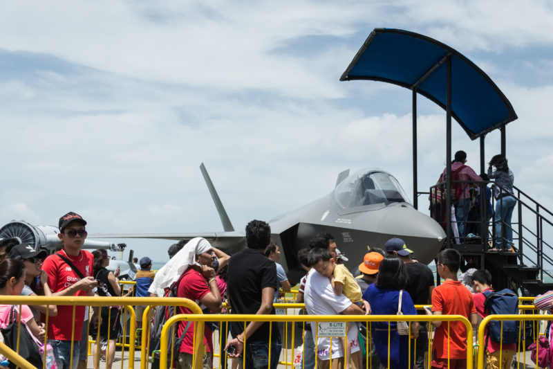 People lining up to enter the cockpit of the F-35B mockup.